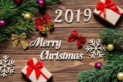 Feliz Navidad 2019 Regalos y malla de la Navidad en el fondo de madera Imagenes de archivo