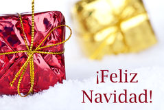 Feliz Navidad in the Snow with Gifts. Christmas Gifts in the Snow with the Spanish Christmas Greetings Feliz Navidad which means Merry Christmas royalty free stock photos