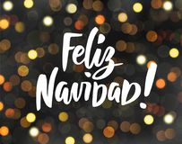 Feliz Navidad - spanish Merry Christmas text. Holiday greetings quote. Glowing golden lights on dark background, bokeh Royalty Free Stock Photography