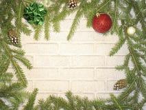 Feliz Navidad - tarjeta de felicitación, árboles de navidad en un fondo del ladrillo Fotografía de archivo