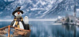 Feliz Navidad un muñeco de nieve con una navegación blanca del búho en el lago de una escena fría del paisaje de la montaña del i fotografía de archivo