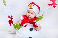 Feliz Navidad y Feliz Año Nuevo bebé feliz en traje del muñeco de nieve Fotografía de archivo