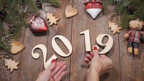 Feliz Navidad y Feliz Año Nuevo 2019 2020 conceptos Las manos femeninas ponen los símbolos de madera 2019 en el fondo de madera d almacen de video