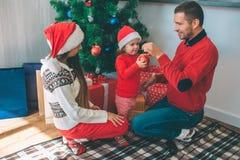 Feliz Navidad y Feliz Año Nuevo Familia feliz que se sienta junto en el árbol de navidad Top del control del hombre joven del jug fotos de archivo