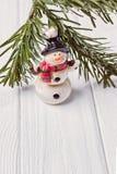 Feliz Navidad y Feliz Año Nuevo Muñeco de nieve y rama de árbol de navidad divertidos en el fondo blanco Espacio libre Fotos de archivo