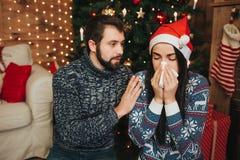 Feliz Navidad y Feliz Año Nuevo Pares jovenes que celebran día de fiesta en casa Mujer joven con el pañuelo Muchacha enferma Imagenes de archivo