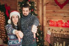 Feliz Navidad y Feliz Año Nuevo Pares jovenes que celebran día de fiesta en casa Pulgar abajo, Año Nuevo, par Imagen de archivo libre de regalías