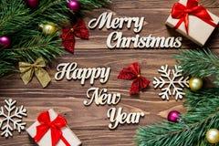 Feliz Navidad y Feliz Año Nuevo Regalos y malla de la Navidad en el fondo de madera Fotos de archivo