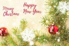 Feliz Navidad y Año Nuevo tipográficos en fondo del día de fiesta con la decoración de Navidad, la rama del árbol de abeto y la n Imágenes de archivo libres de regalías