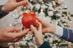 Feliz Navidad y Feliz Año Nuevo una familia feliz que celebra día de fiesta en casa Hombre y mujer que sostienen una bola de la N Foto de archivo libre de regalías
