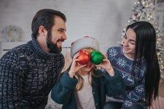 Feliz Navidad y Feliz Año Nuevo una familia feliz que celebra día de fiesta en casa Muchacha de Cild que sostiene una bola de la  Foto de archivo libre de regalías