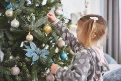 Feliz Navidad y buenas fiestas chica joven que ayudan adornando el árbol de navidad, sosteniendo algunas chucherías de la Navidad Imágenes de archivo libres de regalías