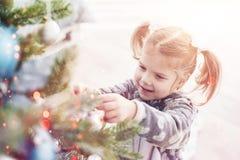 Feliz Navidad y buenas fiestas chica joven que ayudan adornando el árbol de navidad, sosteniendo algunas chucherías de la Navidad Foto de archivo libre de regalías