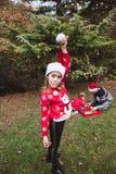 Feliz Navidad y buenas fiestas La muchacha bonita en suéter y sombrero rojos de la Navidad se divierte, y su familia adorna un tr imagenes de archivo