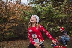 Feliz Navidad y buenas fiestas La muchacha bonita en suéter y sombrero rojos de la Navidad se divierte, y su familia adorna un tr fotografía de archivo libre de regalías