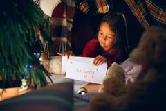 Feliz Navidad y buenas fiestas La muchacha linda del pequeño niño escribe la letra a Santa Claus cerca del árbol de navidad fotografía de archivo libre de regalías