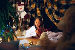 Feliz Navidad y buenas fiestas La muchacha linda del pequeño niño escribe la letra a Santa Claus cerca del árbol de navidad imagen de archivo libre de regalías