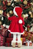 Feliz Navidad y buenas fiestas La muchacha linda del pequeño niño está adornando el árbol de navidad dentro Fotografía de archivo libre de regalías