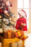 Feliz Navidad y buenas fiestas La muchacha linda del pequeño niño está adornando el árbol de navidad dentro Imagenes de archivo