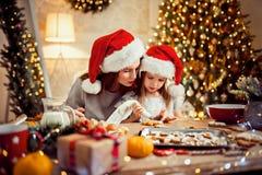 Feliz Navidad y buenas fiestas Madre e hija que cocinan las galletas de la Navidad fotos de archivo libres de regalías
