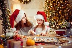 Feliz Navidad y buenas fiestas Madre e hija que cocinan las galletas de la Navidad imágenes de archivo libres de regalías