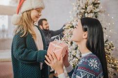 Feliz Navidad y buenas fiestas mamá alegre y su muchacha linda de la hija que intercambian los regalos Padre y pequeño niño foto de archivo
