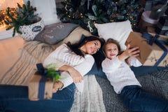 Feliz Navidad y buenas fiestas Mamá alegre y su muchacha linda de la hija que intercambian los regalos Padre y pequeño niño imagenes de archivo