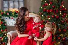 Feliz Navidad y buenas fiestas mamá alegre y su muchacha linda de la hija que intercambian los regalos Padre y poco niño que se d imagenes de archivo