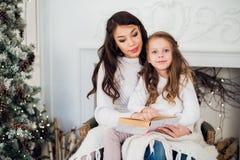 Feliz Navidad y buenas fiestas, mamá bastante joven que lee un libro a su hija linda cerca de árbol dentro Imagenes de archivo