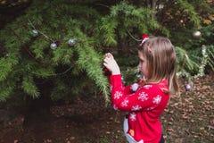 Feliz Navidad y buenas fiestas niña que adorna el árbol de navidad al aire libre en la yarda de la casa antes de días de fiesta fotografía de archivo