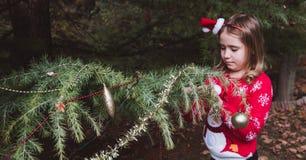 Feliz Navidad y buenas fiestas niña que adorna el árbol de navidad al aire libre en la yarda de la casa antes de días de fiesta fotografía de archivo libre de regalías