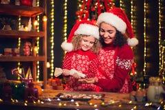 Feliz Navidad y buenas fiestas Niña rizada linda alegre y su más vieja hermana en cocinar de los sombreros de santas imagenes de archivo