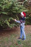 Feliz Navidad y buenas fiestas Padre en sombrero rojo de la Navidad que adorna el árbol de navidad al aire libre en la yarda del  fotos de archivo