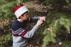 Feliz Navidad y buenas fiestas Padre en sombrero rojo de la Navidad que adorna el árbol de navidad al aire libre en la yarda del  fotografía de archivo libre de regalías