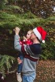 Feliz Navidad y buenas fiestas Padre en sombrero rojo y la hija de la Navidad en suéter rojo que adornan el árbol de navidad al a foto de archivo libre de regalías