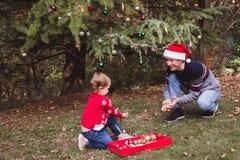 Feliz Navidad y buenas fiestas Padre en sombrero rojo y la hija de la Navidad en suéter rojo que adornan el árbol de navidad al a imagen de archivo libre de regalías