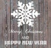 Feliz Navidad y Feliz Año Nuevo en el tablero de madera con el copo de nieve Fotografía de archivo libre de regalías