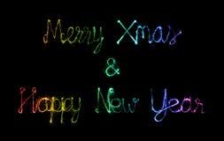 Feliz Navidad y Feliz Año Nuevo hechas del fuego artificial de las chispas Fotos de archivo