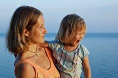 Feliz niña y su madre en la costa Imagen de archivo libre de regalías