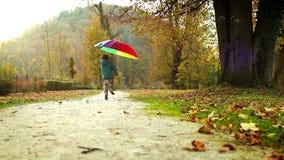 Feliz niño pequeño que salta en un parque con el paraguas multicolor metrajes