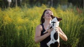 Feliz novo bonito da mulher com o cabelo escuro longo que guarda o cão pequeno no jardim, menina que joga com seu pug no parque vídeos de arquivo