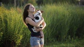 Feliz novo bonito da mulher com o cabelo escuro longo que guarda o cão pequeno no jardim, menina que joga com seu pug no parque filme
