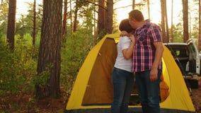 Feliz pareja en los antecedentes de campaña. Pareja enamorada abrazándose al paisaje de sol en el camping. pareja de turistas metrajes