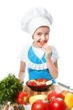 Feliz poco cocinero prueba la ensalada con el paprika Imagenes de archivo