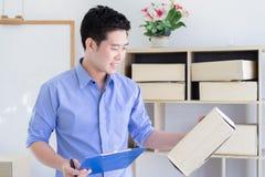 Feliz posea al hombre de negocios que comprueba orden y que embala para hacer compras en línea en casa oficina imágenes de archivo libres de regalías