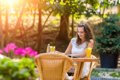 Feliz, positivo, bonito, a menina da elegância que senta-se no café apresenta fora Imagens de Stock Royalty Free