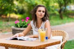 Feliz, positivo, hermoso, la muchacha de la elegancia que se sienta en el café presenta al aire libre Foto de archivo