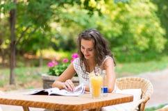 Feliz, positivo, hermoso, la muchacha de la elegancia que se sienta en el café presenta al aire libre Fotografía de archivo libre de regalías