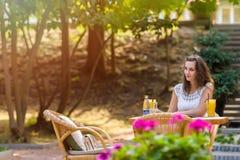 Feliz, positivo, hermoso, la muchacha de la elegancia que se sienta en el café presenta al aire libre Fotos de archivo libres de regalías