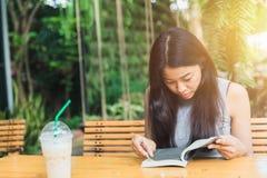 Feliz relaje las épocas con el libro de lectura, sonrisa adolescente tailandesa de las mujeres asiáticas con el libro en jardín Imagenes de archivo